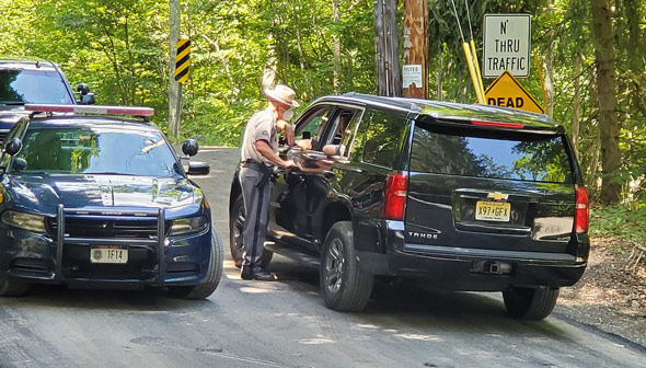 new york state troopers closed off the area near where suspected gunman roy den hollander was found dead